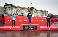 4th October 2020, London, England; 2020 London Marathon; Sara Hall (USA) (left, second place), Brigid Kosgei (KEN) (centre, winner) and Ruth Chepngetich (KEN) (right, third place) on the podium outside Buckingham Palace with their trophies for the Elite Women's Race. The historic elite-only Virgin Money London Marathon taking place on a closed-loop circuit around St James's Park in central London on Sunday 4 October 2020.