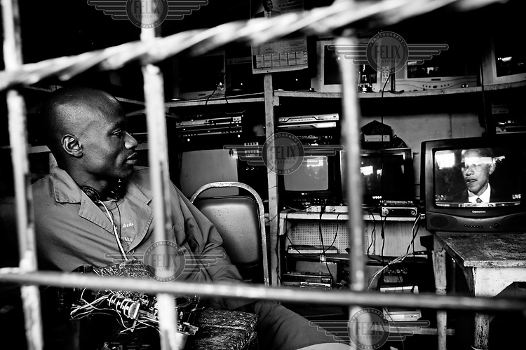 The owner of a TV repair shop in Kibera watches as the election victory speech by US President elect Barack Obama is broadcast live via satellite.