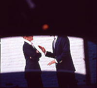 Man & Woman executives in suits arguing, seen through limousine window<br />