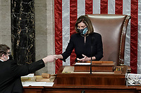 Speaker of the United States House of Representatives Nancy Pelosi (Democrat of California) is handed the vote count for H.R. 24, an article of impeachment against President Donald Trump, on Wednesday, January 13, 2021 in the House Chamber at the U.S. Capitol.<br /> Credit: Greg Nash / Pool via CNP /MediaPunch