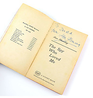 """BNPS.co.uk (01202) 558833. <br /> Pic: Ewbanks/BNPS<br /> <br /> Pictured: Also included in the sale is this fifth issue of a 1963 printing by Signet of The Spy Who Loved Me includes an inscription by the author reading """"To Donald from Ian Fleming"""". Estimate is £1,500.<br /> <br /> A rare movie poster for the James Bond film Thunderball that was designed to be torn into four pieces is tipped to sell for £12,000.<br /> <br /> The quad poster contains four individual works of art promoting the 1965 movie.<br /> <br /> The panels show Sean Connery as 007 flying through the air in a jet suit, being mobbed by glamorous women, fighting a scuba diver and sat on a beach poised with weapon in hand."""