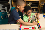 Education Preschool 4 year olds two boys playing together with colored plastic bears, talking