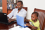 3 year old boy at home with his father modeling imitation father working on paperwork from job and using laptop computer boy using toy computer horizontal