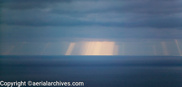 aerial photograph of shafts of light passing through fog on Pacific Ocean off the California coast