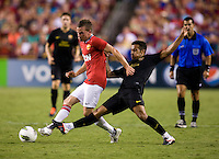 Tom Cleverly (35) of Manchester United passes the ball away from Thiago (4) of Barcelona during the friendly at FedEX Field in Landover, MD.  Manchester United defeated FC Barcelona, 2-1.