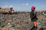 13 february 2013 - Dandora dumpsite, Nairobi, Kenya - A young Kenyan woman eats an ice-cream at the Dandora dumpsite, one of the largest and most toxic in Africa. Located near slums in the east of the Kenyan capital Nairobi, the open dump site was created in 1975 and covers 30 acres. The site receives 2,000 tonnes of unfiltered garbage daily, including hazardous chemical and hospital wastes. It is a source of survival for many people living in the surrounding slums, however it also harms children and adults' health in the area and pollutes the Kenyan capital. Photo credit: Benedicte Desrus