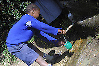 In Naro Moru, a small rural village on the slopes of Mount Kenya, in Kenya, East Africa, a young primary school student pours clean drinking water from the school's new Rainwater Storage Tank.  Prior to receiving this tank, these children got their water from a rivers laden with wildlife and their excrements.
