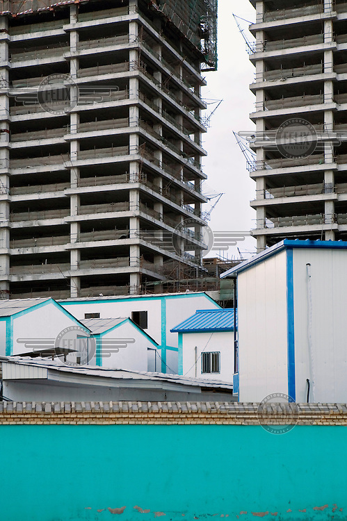 Workers' accommodation and a Chinese traditional style wall on a construction site.
