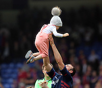 Pictured: A Crystal Palace player withwith his young baby thanks supporters at the end of the game<br />