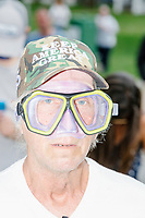 """A man wears a camouflage Trump campaign hat reading """"Keep America Great"""" and swimming goggles as people gather for an anti-lockdown protest organized by the alt-right group Super Happy Fun America near the home of Massachusetts governor Charlie Baker in Swampscott, Massachusetts, on Sat., May 16, 2020. The protest was in defiance of Massachusetts orders mandating face coverings and social distancing and prohibiting gatherings larger than 10 people during the ongoing Coronavirus (COVID-19) global pandemic. The state's stay-at-home order is expected to be updated on May 18, 2020, with a phased reopening plan issued by the governor as COVID-19 cases continue to decrease. Anti-lockdown protests such as this have become a conservative cause and have been celebrated by US president Donald Trump. Many of the protestors displayed pro-Trump messages or wore Trump campaign hats and shirts with phrases including """"Trump 2020"""" and """"Keep America Great."""" Super Happy Fun America, organizers of the protest, are an alt-right organization best known for creating the 2019 Boston Straight Pride Parade."""