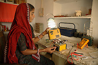 Kamla, age 33, is Rajasthan's first female solar engineer. Starting her education at age 11 in night school, while carrying on with her domestic and farm work, she went on to study solar technology and now runs a rural field station fabricating solar home lighting systems and solar lanterns. Despite her humble background she has travelled to Delhi to speak at National Conferences on solar technology. Here, Kamla repairs a solar lantern in her workshop...