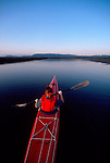 Woman sea kayaker, Puget Sound, Skagit Bay, Washington State, Pacific Northwest, view from above, paddling into the wilderness,