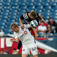 FOXBOROUGH, MA - JULY 23: Garrett McLaughlin #49 of Toronto FC II and Pierre Cayet #44 of New England Revolution II battle for head ball during a game between Toronto FC II and New England Revolution II at Gillette Stadium on July 23, 2021 in Foxborough, Massachusetts.