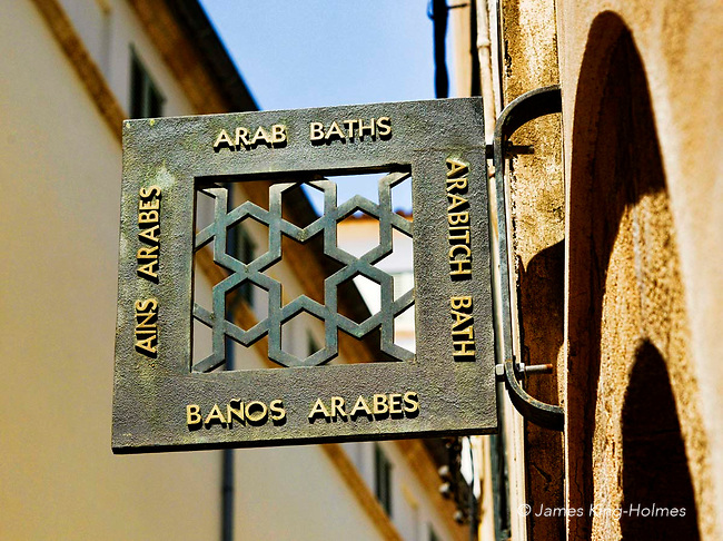 Sign at the entrance to the Banos Arabes, or Arabic Baths, in Palma de Mallorca. This building and garden is one of the few monuments to the arabic period of the island.