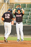 Adam Heisler (6) of the Kannapolis Intimidators waits to high five teammate Michael Marjama (12) as he crosses home plate after hitting a 2-run home run against the Lakewood BlueClaws at CMC-Northeast Stadium on August 14, 2013 in Kannapolis, North Carolina.  The Intimidators defeated the BlueClaws 10-2.  (Brian Westerholt/Four Seam Images)