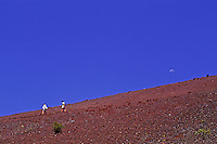 Hiking on the red moonlike landscape of Sliding Sands Trail against a brilliant blue sky in Haleakala National Park on Maui.