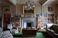 The library is more obviously Edwardian in its period, unlike many of the other remodelled rooms. Its modest fireplace decorated with blue, white and yellow tiles is flanked by matching carved bookcases