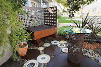 Circular seating patio with wooden bench using salvaged perforated backing, Matthew Levesque garden, repurposed, recycled garden material
