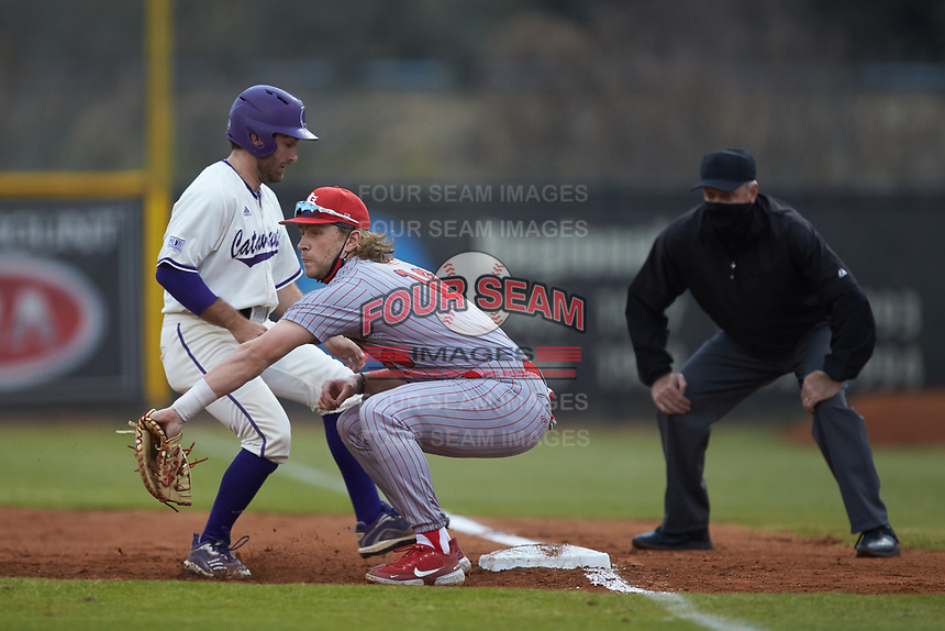 St. John's Red Storm first baseman David Williams (16) fields a pickoff throw as Seth Graves (33) of the Western Carolina Catamounts gets back to the bag safely at Childress Field on March 13, 2021 in Cullowhee, North Carolina. (Brian Westerholt/Four Seam Images)