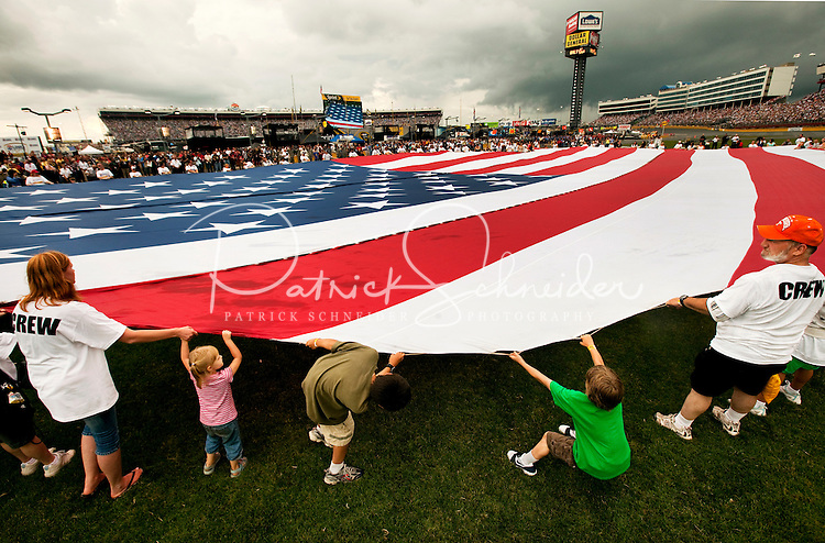 Participants work to hold up a giant American flag during opening ceremonies of the Coca-Cola Classic 900 NASCAR Race at the Lowe's Motor Speedway, in Concord, NC, held on Memorial Day 2009. Driver David Reutimann won his first Cup race during the rain-shortened event, held May 25, 2009. NASCAR's longest scheduled race went only 227 laps, or 340.5 miles, before officials ended it because of rain. The 2009 race was the 50th running of the Coca-Cola 600. Ryan Newman and Robby Gordon finished second and third respectively.