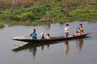 Myanmar, Burma.  Mother and Children in Canoe, Paddling, Inle Lake, Shan State.