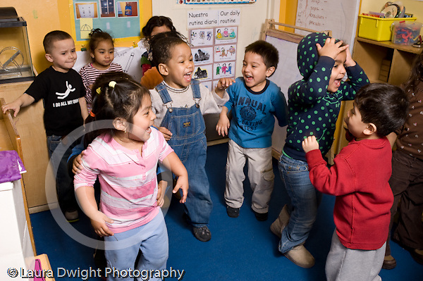 Educaton preschool  3-4 year olds movement dancing exercise group of children dancing to music horizontal one boy in background not participating