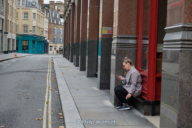 Woman smoking outside Cafe Rouge, Carter Lane, City of London.  Empty streets at lunchtime.
