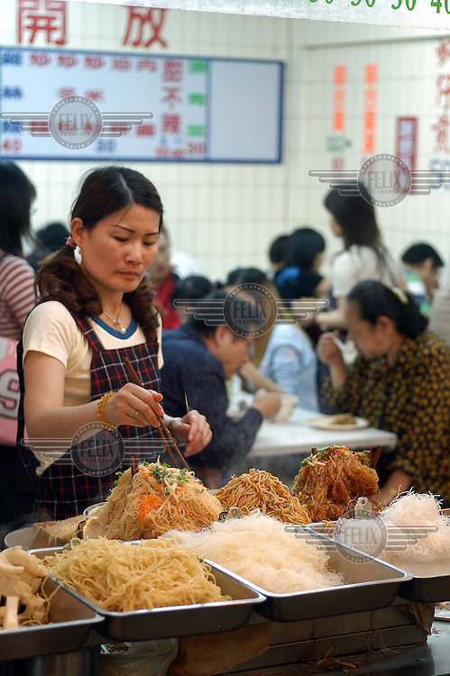 Steaming piles of noodles on sale in a cafeteria at Gongguan Night Market.