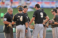 Head coach Todd Interdonato of the Wofford Terriers talks with pitcher Matthew Milburn (24) in a SoCon Tournament game against Western Carolina on Wednesday, May 25, 2016, at Fluor Field at the West End in Greenville, South Carolina. Western won, 10-9. (Tom Priddy/Four Seam Images)