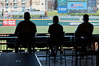 Three fans watch the Southern Collegiate Baseball League game between the Concord Athletics and the Piedmont Pride from the concourse area at Truist Field on July 3, 2020 in Charlotte, NC. Truist Field is allowing restaurant reservations  with no more than 25 people to a space to encourage proper social distancing. The seating bowl is closed to fans at this time. (Brian Westerholt/Four Seam Images)