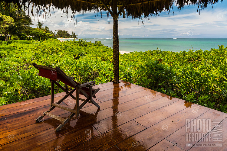 An available beach chair under a thatched roof overlooking Waialua Beach, North Shore, O'ahu.