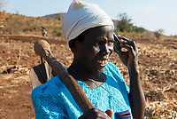 MALAWI, village Zingiziwa, woman with hoe and mobile phone / MALAWI, Dorf Zingiziwa, Farmerin mit Hacke und Mobiltelefon