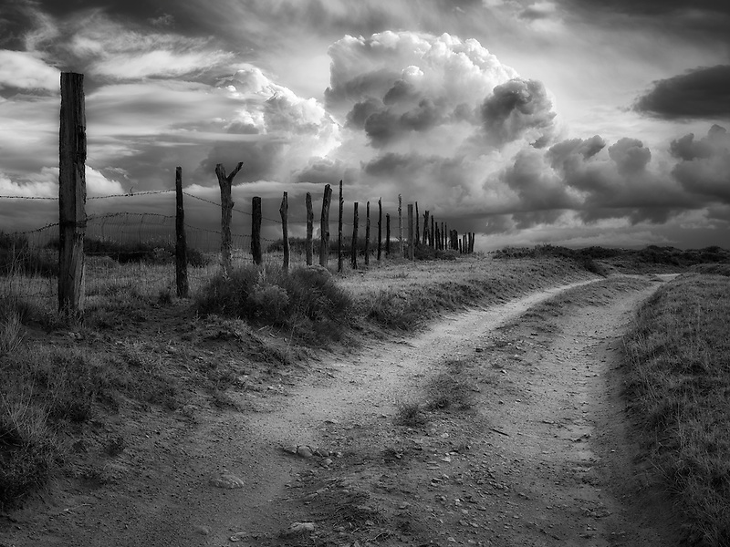 Road, fenceline and thunderstorm near Coal Mine Canyon, Arizona