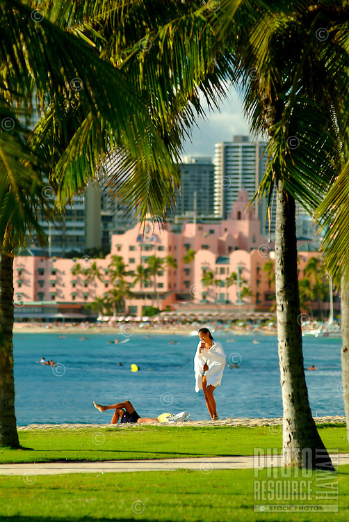 """A woman strolls along a palm tree lined path off  Waikiki Beach with the blue ocean and the Royal Hawaiian Hotel, or """"""""pink palace"""""""" in the background."""
