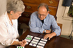 Senior couple sitting at table together playing pattern recognition card game Caucasian horizontal