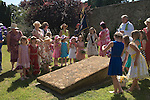Nether  Stowey Female Friendly Society ( The Womens Walk ) Club Day. Local women and flower girls walk from the village to the grave of Tom Poole the founder of the society in 1806. The Rev Craig Marshall St Mary's Church where a prayer is said around the grave followed by a church service. Nether Stowey Somerset UK 2014. 208th Club day walk.