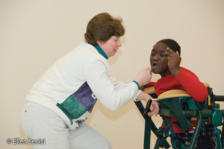 MR / Albany, NY.Langan School at center for Disability Services (Private nonprofit disability services).Upper elementary classroom / Day Program.Physical therapist communicates with child in a gait trainer. Girl: 10, African-American, cerebral palsy, expressive and receptive language delays.MR:Pie3; And6.© Ellen B. Senisi