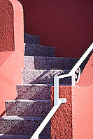 A fine art abstract of stairs typical of the Sunset District in San Francisco, with stucco stair walls painted bright orange and the steps a soft purple.  Late afternoon shadows change the hue of some of the mauve steps and orange rear wall.