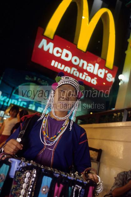 Asie/Thaïlande/Chiang Mai : Dans le Night Bazaar femme Karen vendant des bijoux devant l'enseigne du Mac Donald