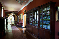 A long, glass fronted cabinet used to display a large collection of china in an upstairs corridor