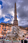 The Fountain of Four Rivers in the center of the colorful Piazza Navona (Rome, Italy) was sculpted by Gian Lorenzo Bernini in 1651.  The fountain is topped by the Obelisk of Domitian.  (HDR image)