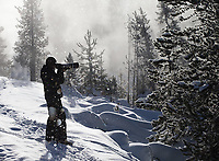 A photographer shoots landscapes during a light snowfall in Yellowstone.