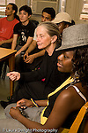 Education High School public female English teacher and students listening in class as someone out of view speaks vertical