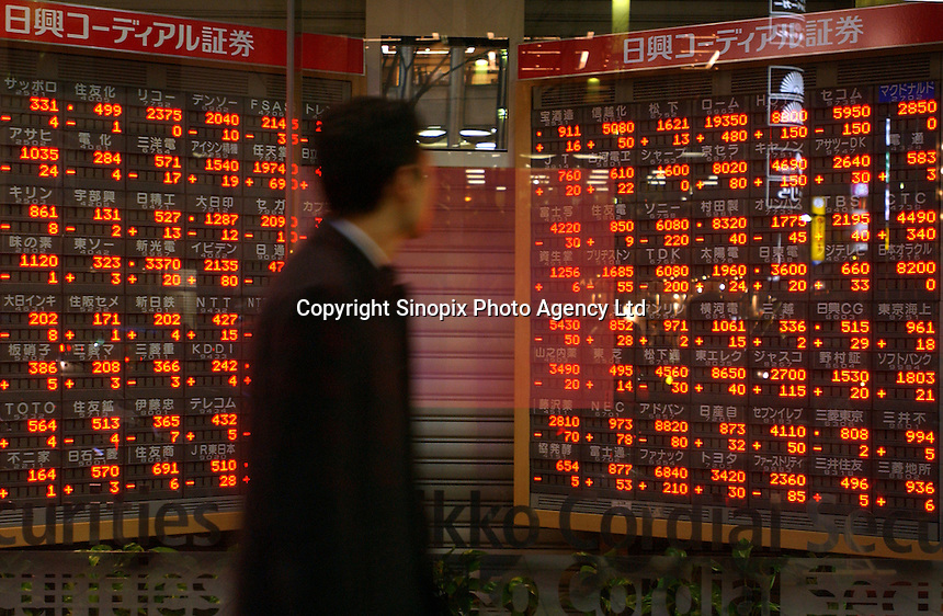 Businessmen pass a stock market sign board in the window a Nikkei Securities company in the Ginza district of Tokyo..