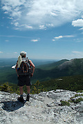 A hiker takes in the view of Charles Ravine from Baldface Circle Trail in the scenic landscape of the White Mountains, New Hampshire USA during the spring months. .