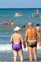 Italy. Province Emilia-Romagna. Rimini. A couple of elderly italian tourists hold each other by the hands and enjoy the water on the sandy beach. Life in the summer on the beach. Rimini is located on the Adriatic Sea and is one of the most famous seaside resorts in Europe, thanks to its 15 km-long sandy beach. 17.07.99 © 1999 Didier Ruef