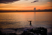 Children swimming on the Malecon at sunset