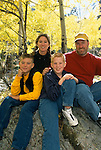 A portrait of a family of four underneath fall-colored aspen trees in the Rocky Mtns of Colorado.