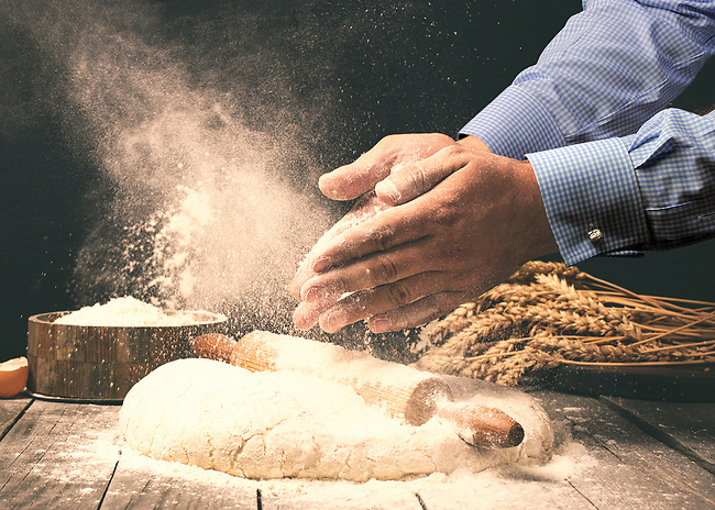 Man preparing bread dough on wooden table in a bakery close up with added dress shirt and cufflinks.