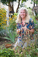 Tammi Hartung gathering seed in her herb garden